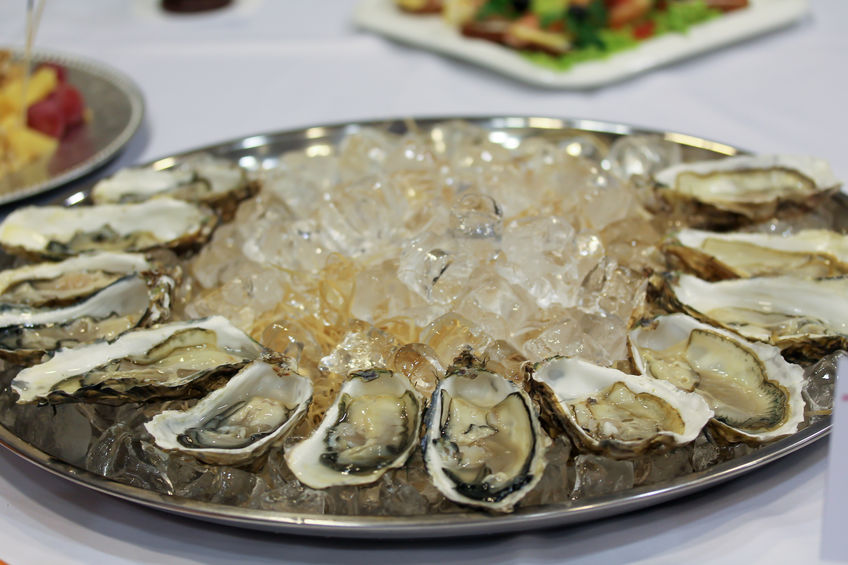 Oysters with ice cubes on the big silver or metal round plate. Seafood served in buffet. Expensive delicacy on the table. Fine food photography. Catering service at the party or dinner